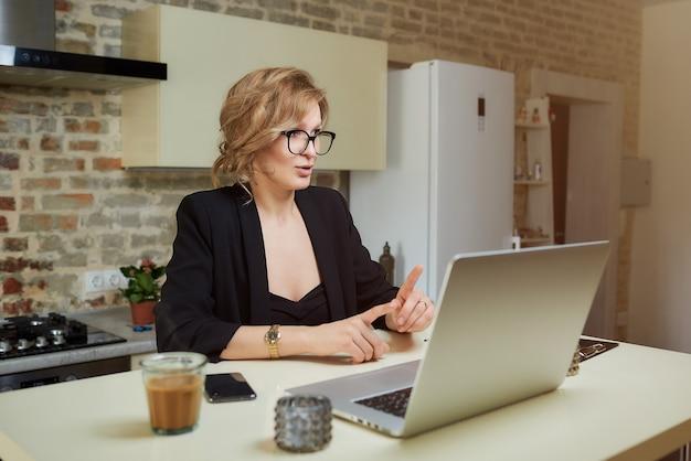 Una giovane donna con gli occhiali lavora a distanza su un laptop nella sua cucina. una ragazza con le parentesi graffe gesticolano mentre parla con i suoi colleghi in una videoconferenza a casa.