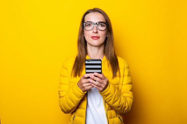 Giovane donna in occhiali e giacca gialla