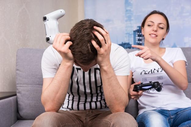 Giovane donna che gongola dopo aver vinto un videogioco indicando suo marito con un sorriso mentre si tiene la testa per la vergogna e la frustrazione
