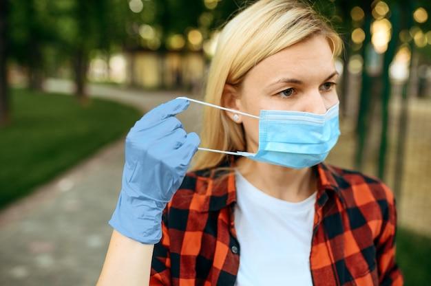 Giovane donna in guanti mette la maschera sul viso nel parco, quarantena. persona di sesso femminile che cammina durante l'epidemia, assistenza sanitaria e protezione, stile di vita pandemico