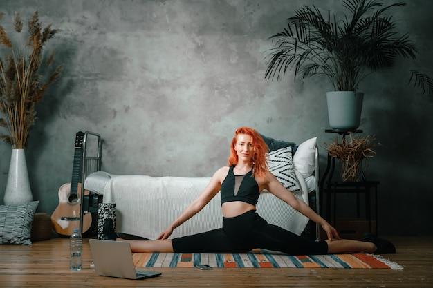 Una giovane donna fa sport a casa, allenamento online. l'atleta si stiracchia, medita, seduto su uno spago in camera da letto, sullo sfondo c'è un letto, un vaso, un tappeto.