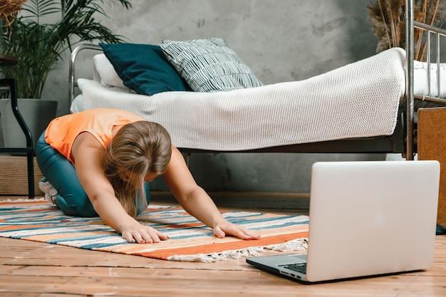 Una giovane donna va a fare sport a casa, allenamento online