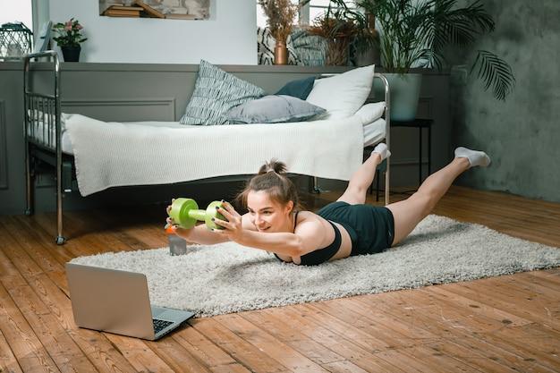 La giovane donna fa sport a casa. uno sportivo con i capelli neri fa una tavola, solleva braccia e gambe con un manubrio, guarda un film e studia da un laptop sul tappeto in camera da letto