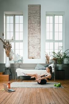 La giovane donna va a fare sport a casa, allenandosi online. l'atleta fa la stampa, alza le gambe, guarda un film e social network sul laptop