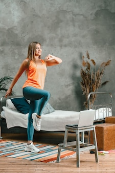 La giovane donna va a fare sport a casa, allenandosi online
