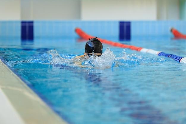 Giovane donna in occhiali e berretto da nuoto stile rana nella piscina da gara coperta di acqua blu.