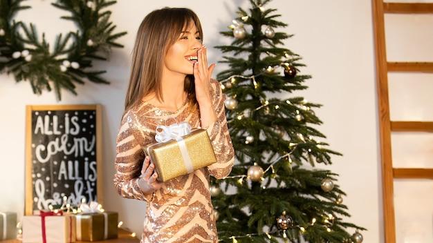 Una giovane donna con un abito festivo dorato tiene in mano una scatola con un regalo