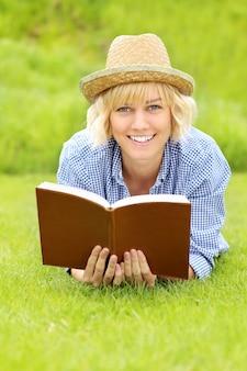 Una giovane donna su un prato con un libro