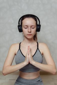 Giovane donna in abiti sportivi grigi che fa yoga su un tappeto a casa in cuffie