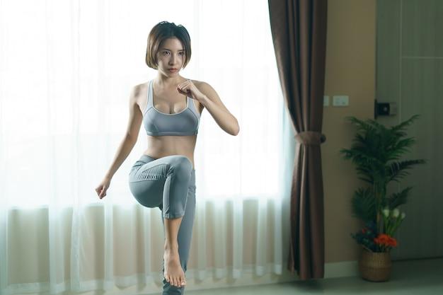 Giovane donna in abbigliamento sportivo grigio a casa, facendo ginocchio alto