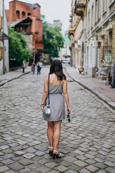 Giovane donna in un prendisole grigio durante un tour della città