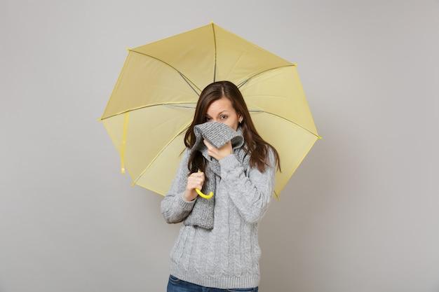 Giovane donna in maglione grigio che copre la bocca, viso con sciarpa che tiene ombrello giallo isolato su sfondo grigio muro. concetto di stagione fredda di emozioni della gente di stile di vita sano di modo. mock up copia spazio.
