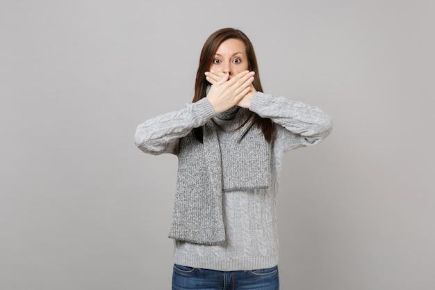Giovane donna in maglione grigio, sciarpa che copre la bocca con le mani isolate su sfondo grigio, ritratto in studio. stile di vita sano, persone sincere emozioni, concetto di stagione fredda. mock up copia spazio.