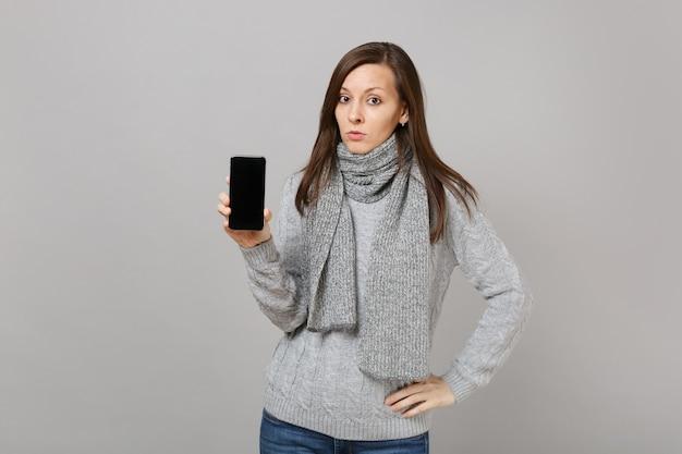 Giovane donna in maglione grigio, sciarpa che tiene il telefono cellulare con schermo vuoto vuoto isolato su sfondo grigio. stile di vita sano persone emozioni sincere, concetto di stagione fredda. mock up copia spazio.