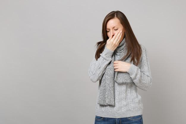 Giovane donna in maglione grigio sciarpa starnuti o tosse che copre la bocca con il palmo isolato su sfondo grigio muro. trattamento di malattia malato malato di stile di vita sano, concetto di stagione fredda. mock up copia spazio. Foto Premium