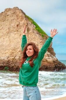 Una giovane donna in giacca verde cammina lungo la pittoresca spiaggia di shark fin bay in california