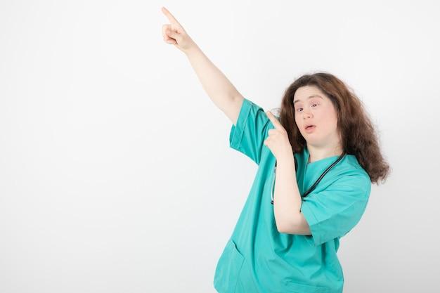 Giovane donna in uniforme verde in piedi e che punta lontano.