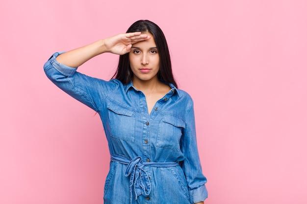 Giovane donna saluto con un saluto militare in un atto di onore e patriottismo, mostrando rispetto