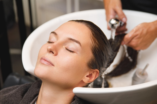 Giovane donna nel parrucchiere durante il lavaggio dei capelli dopo il taglio di capelli