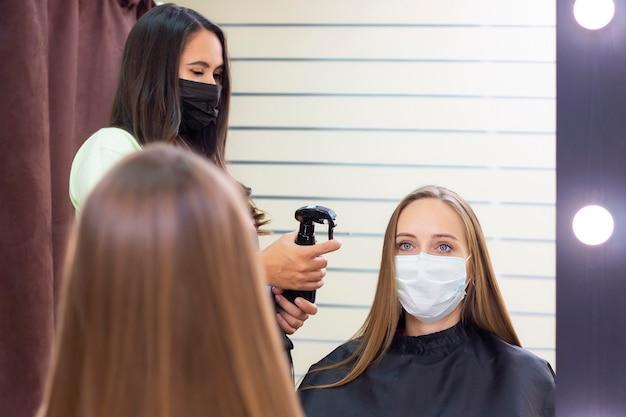Giovane donna al parrucchiere che indossa una maschera protettiva a causa di una pandemia di coronavirus
