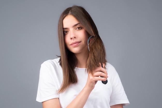 Parrucchiere della giovane donna con il pettine che spazzola i capelli