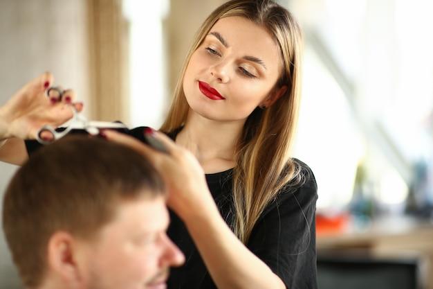 Parrucchiere di giovane donna che taglia i capelli del cliente maschio