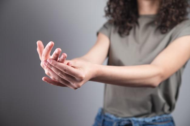 Mano della giovane donna nel dito di dolore.