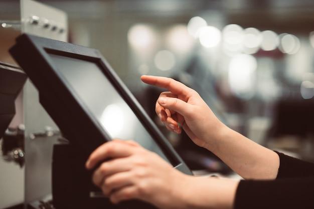Mano della giovane donna che fa il pagamento di processo su un registratore di cassa dello schermo attivabile al tatto, concetto di finanza