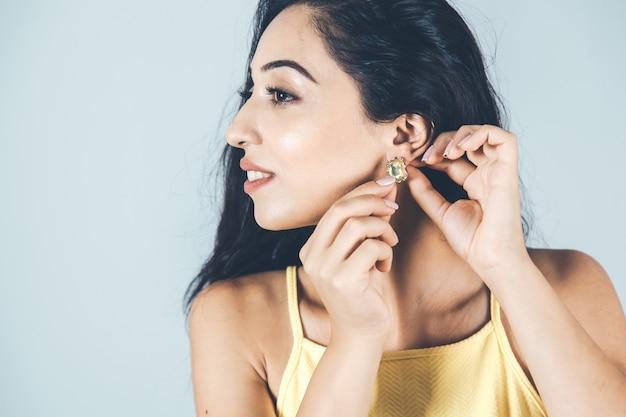 Orecchino della mano della giovane donna nell'orecchio