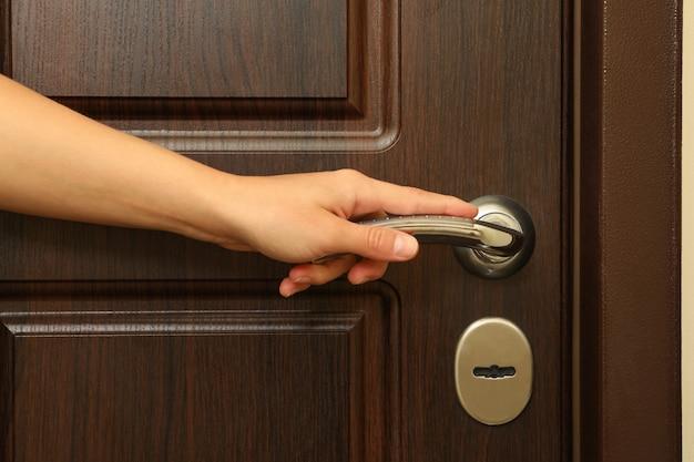 Maniglia della porta di legno della stretta della mano della giovane donna