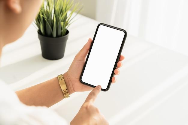 Giovane donna mano che tiene smartphone sul tavolo e lo schermo è vuoto, concetto di rete sociale.