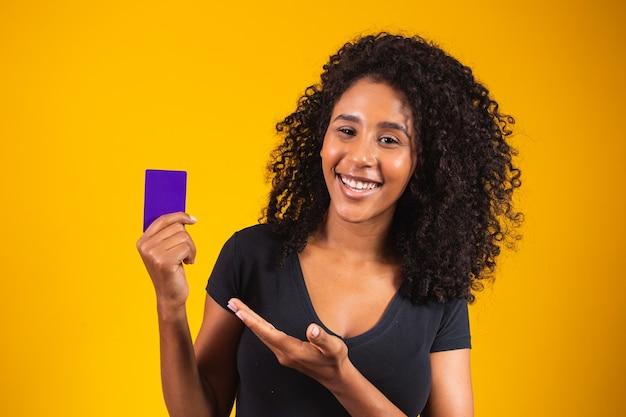 La mano della giovane donna tiene il modello di carta viola. scheda di acquisto della holding della donna. bella giovane donna in possesso di carta di credito bancaria