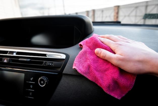 Mani della giovane donna che puliscono la polvere della sua auto con un panno rosa.