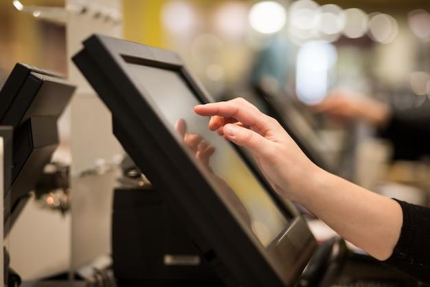 Mani della giovane donna che contano entrando in vendita di sconto a un registratore di cassa touchscreen