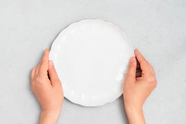 La giovane donna passa la tenuta del piatto vuoto bianco