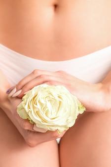 Mani della giovane donna che tengono un fiore bianco che copre la zona bikini di epilazione isolata