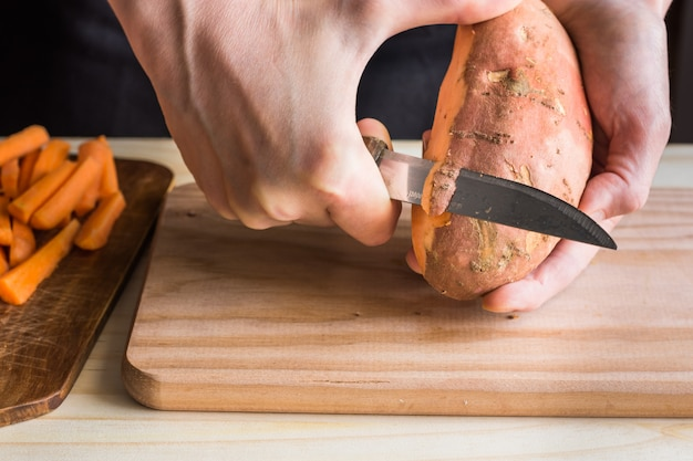 La giovane donna passa la sbucciatura con la patata dolce del coltello sopra il tagliere di legno