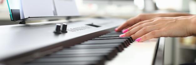 Mani della giovane donna suonare il pianoforte a casa