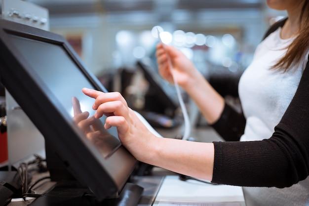 La giovane donna passa la scansione / immissione dello sconto / vendita su una ricevuta, registratore di cassa touchscreen, mercato / negozio
