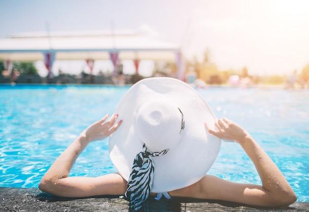 Giovane donna felice in grande cappello che si distende sulla piscina