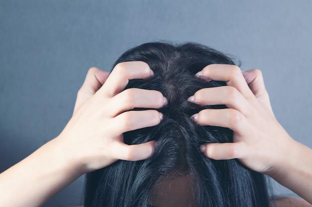 Una giovane donna ha prurito alla testa