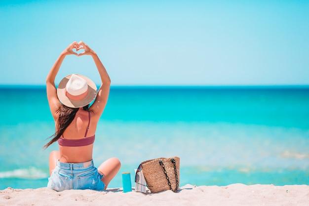 Giovane donna in cappello sulla vacanza al mare
