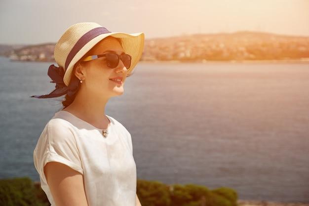 Giovane donna con cappello e occhiali sullo sfondo del mare., luce solare