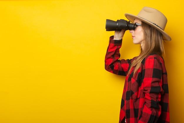 Giovane donna in cappello e camicia a quadri guardando attraverso il binocolo su sfondo giallo.