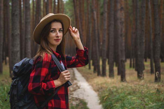 Giovane donna in cappello, camicia rossa e zaino nella foresta. escursione nella foresta.