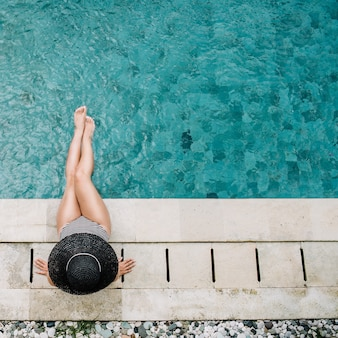 Giovane donna in cappello che si distende vicino alla piscina vista dall'alto