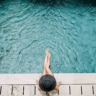 Giovane donna in cappello che si distende vicino alla piscina