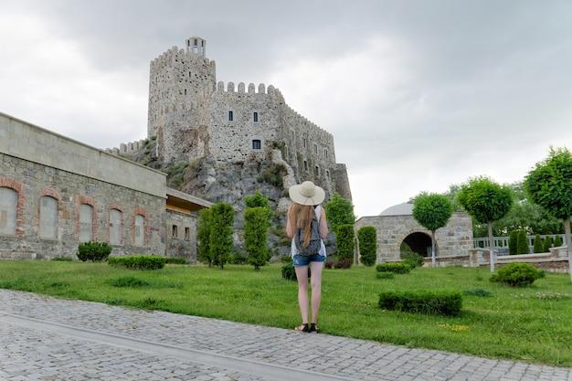 Giovane donna in un cappello con uno zaino e una fortezza in lontananza