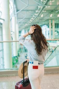 Giovane donna con cappello con bagaglio in aeroporto internazionale a piedi con i suoi bagagli.