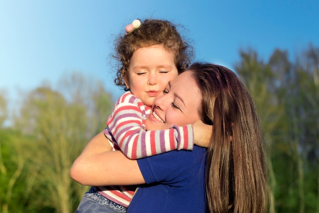 La giovane donna si diverte, abbracciando la sua bambina bambino carino. ritratto della madre, figlia del bambino all'aperto al giorno soleggiato di estate. festa della mamma, amore, felicità, famiglia, genitorialità, concetto di infanzia